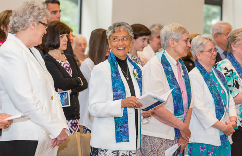 Sister Arlene Antczak, OP, former prioress (far left), and Sister Patrice Werner, OP, prioress, share a moment during the Mass of Transition. Photo by Pushparaj Aitwal.