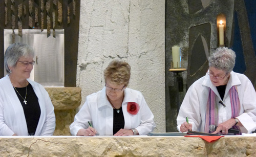 Sister Kathy Flynn, OP, signs profession documents with Sister Mary Ellen Gevelinger, OP, and Sister Mary Ann Nelson, OP