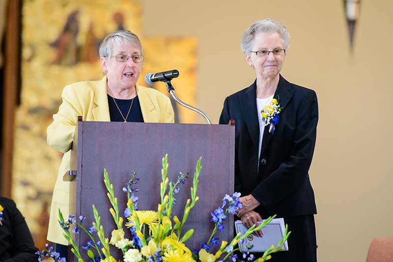 Sister Fran Nadolny, OP, Administrator and General Councilor of the Adrian Dominican Sisters, introduces Sister Catherine DeClercq, OP, Outstanding Alumni Award recipient at Siena Heights University. (Photo by Laura Marsh, of Siena Heights University)